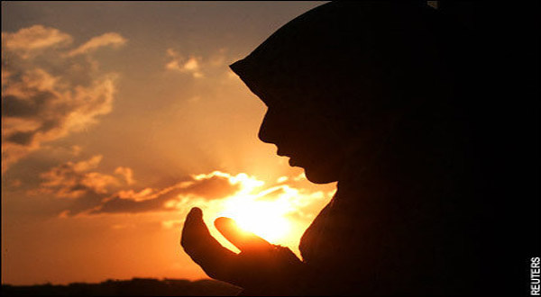 A Muslim woman raising her hands in supplication.