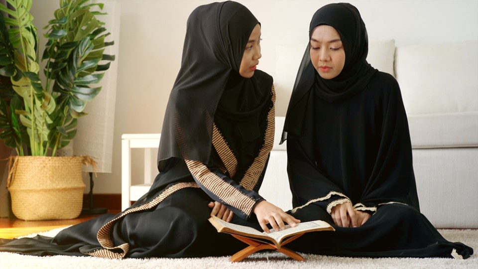 Two Muslim women wearing Hijab and reading the Qur'an whose verses urges chastity and modesty.
